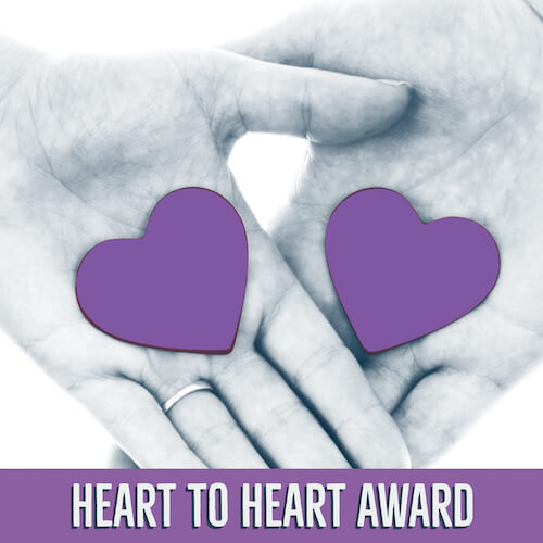 Two hands layed on top of each other with purple hearts in their palms